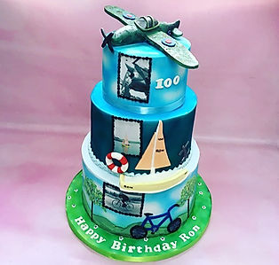 Luxury birthday cakes from Sussex cake maker Calleys Cakes. High end birthday cakes delivered. Three tier birthday cake with sailing themed birthday cake cycling themed birthday cake an RAF plane flying birthday cake topper.  The cake features edible photo prints