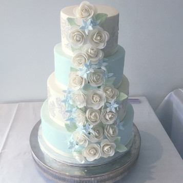 Ivory and blue wedding cake, rose cascade wedding cake, pale lue wedding cake, ivory wedding cake, roses wedding cake, floral wedding cake, wedding cake with flowers, four tier wedding cake, east sussex national wedding cake