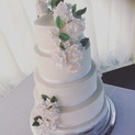 White wedding cake with sugar flower spray at Slaugham Place