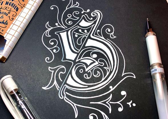 Ornamentbuchstabe S in weiß auf schwarze