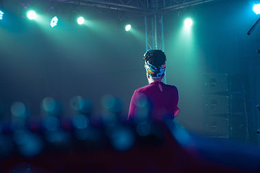 An image from behind of a Black woman wearing a headwrap standing on a stage.