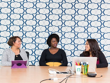 Three women sit at a work desk. They are in conversation