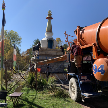 The truck mixing and filling the stupa with cement