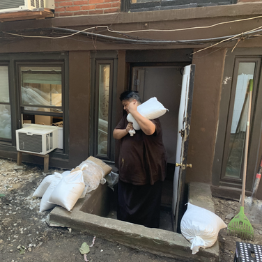 Rinpoche carrying a bag of sand