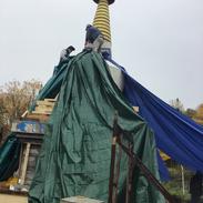 Volunteering Sangha Members help to lay bricks and cement on the stupa