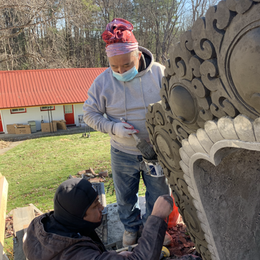 Lopon Jampal carving the window of the stupa's bumpa section with the help of Lama Dorji