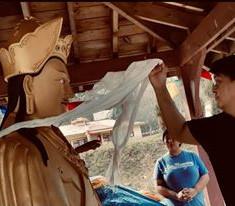 Rinpoche taking khata off of Guru Rinpoche's Ku