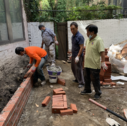 Karmarong laying bricks for the flower bed
