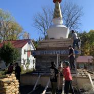 Volunteering Sangha Members helping to lay cement on the stupa