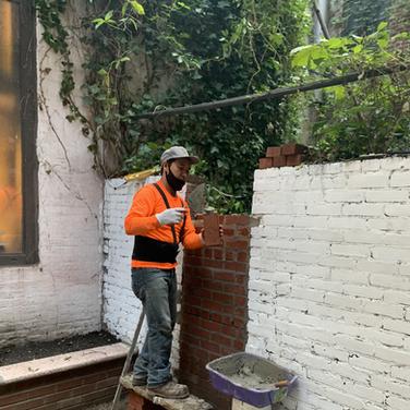 Dawa Tsering laying bricks to patch up the backyard garden wall