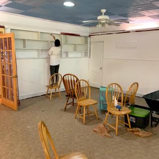 Misun painting the bookshelves