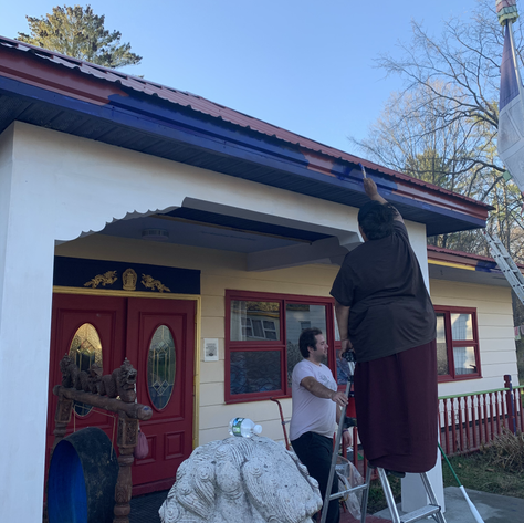 Rinpoche painting the trim of the Main Temple, while John assists him