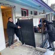 Lopon Lulu and Misun bringing the bed frame out of Buddha House's number 5