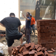 Karmarong preparing materials to lay bricks for the flower bed