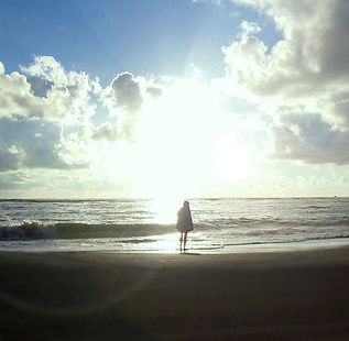 Woman on beach with sun halo | Contemplative Marketing for Your Heat-Centered Offerings | Sandra Mitchell | Writer. Marketer, Coach. | West Michigan Lakeshore