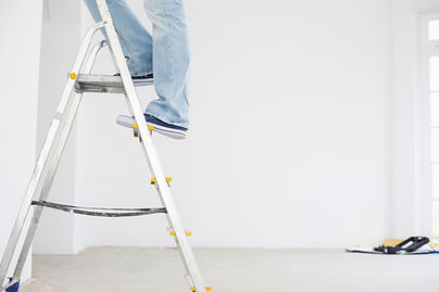 A man going up a ladder to take down curtains from the curtan rail.