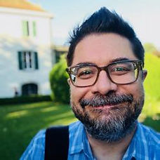 Christopher Bavitz, a oldewhite man with glasses and a beard, smiles at the camera, selfie-style.