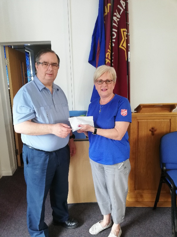 Steve Wright presents a cheque to Major Dawn Lacey of the Salvation Arm