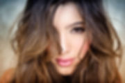 Close Up of a Beautiful Latina Woman with brown eyes and luscious lips with hair covering half her face