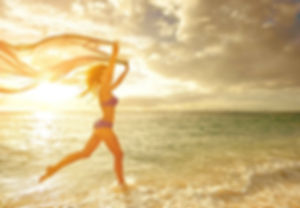 A thin fit woman dancing in the water close to the beach at sunset in a Purple swim suit as her hair blows back with the wind