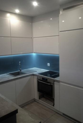 Zabudowa kuchenna biały połysk z wstawionym pomiędzy szafkami szkłem w kolorze morskim.