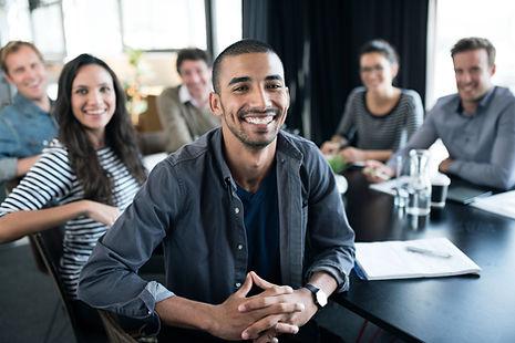 Lächelndes Team an einem Tisch, das in die Kamera blickt.