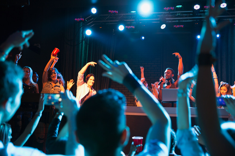 a stage with a DJ and people standing around the stage waving their arms and hands up