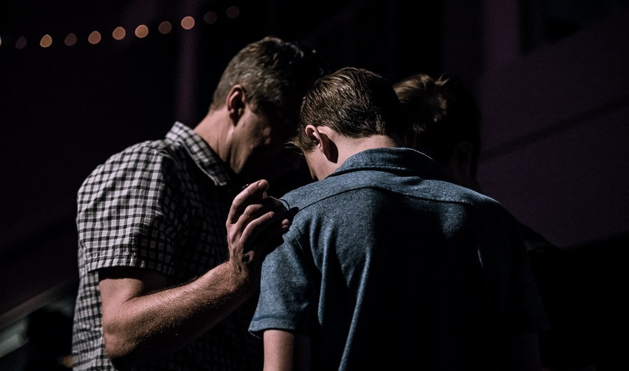 Two men pressing their heads together in prayer