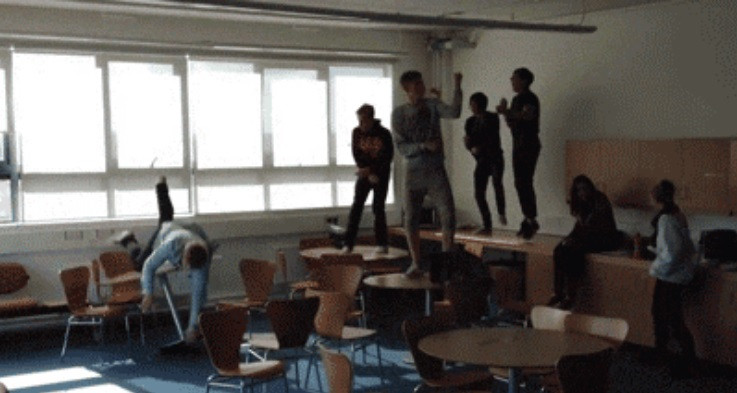 Kids dancing on desks with one falling.