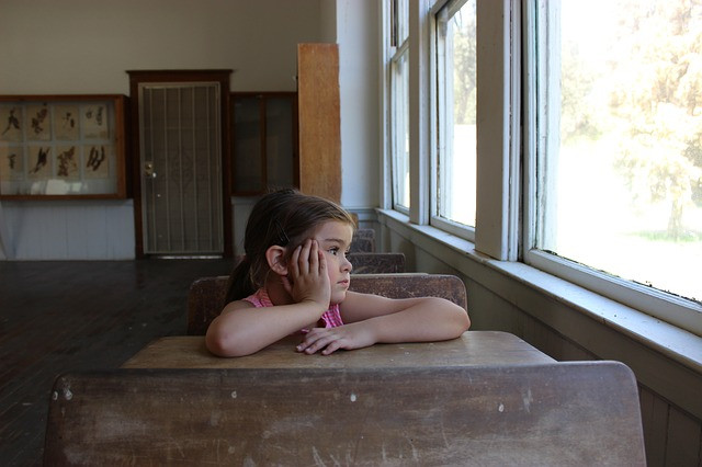 Young girl sitting at a desk depressed