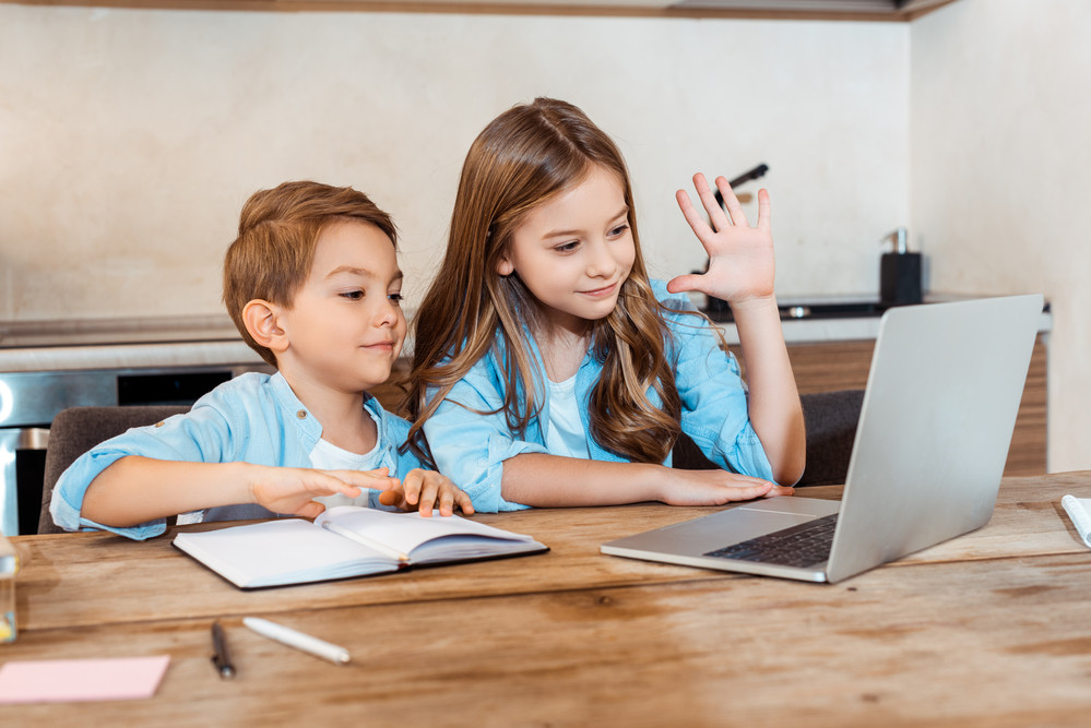 Children learning through remote education with a laptop