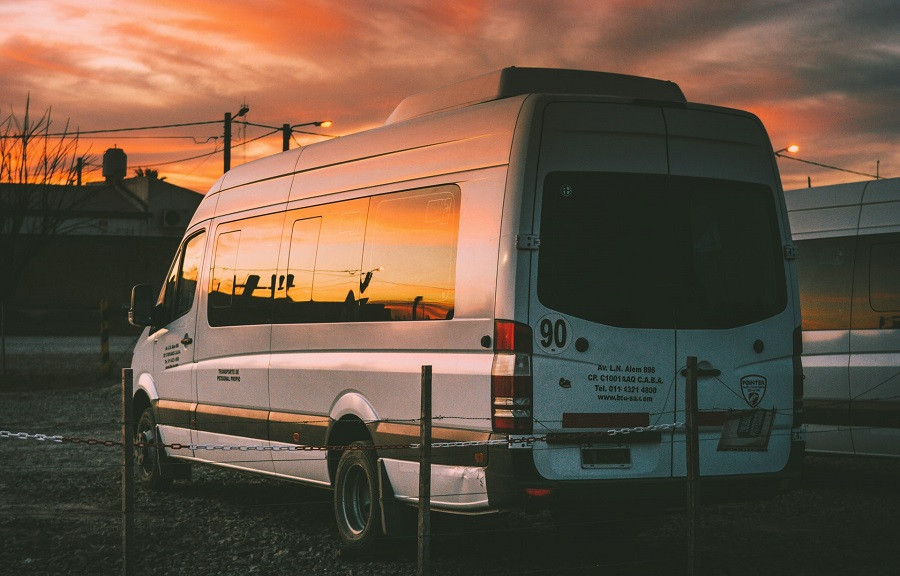 Church van parked in a field at sunset