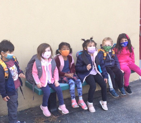 Admissions-children inside on bench with backpacks 5.2021.JPG