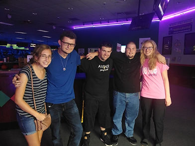 Michael poses with his friends at a bowling alley