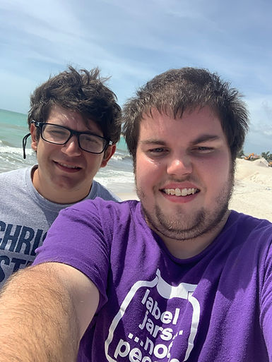 Michael and his friend smile at the beach.