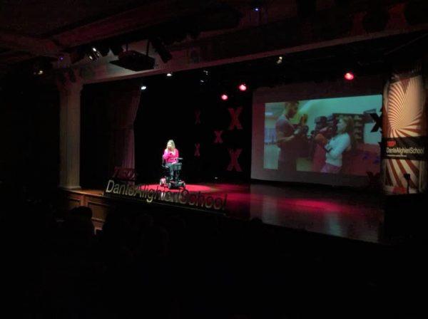 Nathalia no palco do TEDx, com blusa rosa e em frente de um telão com imagens da sua vida!
