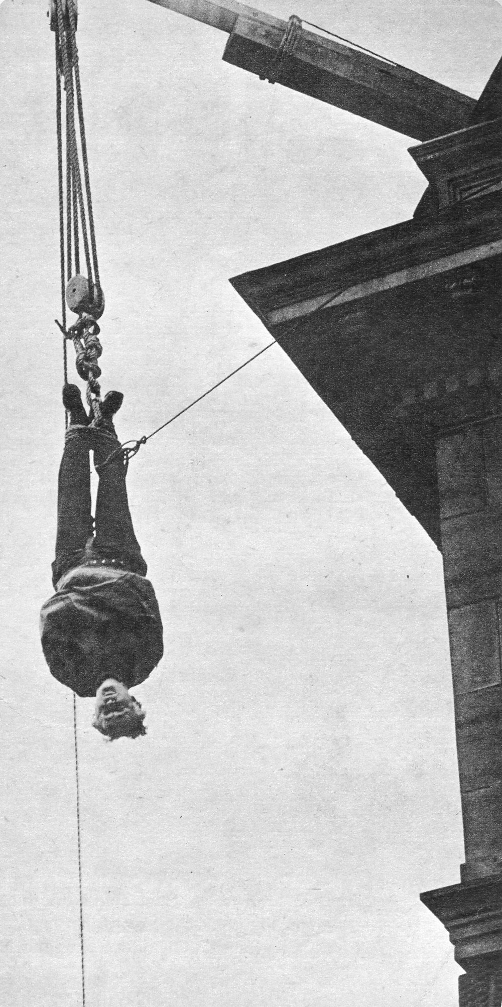 Harry Houdini hanging upside down for a stunt