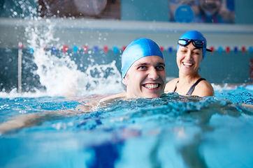 Female Swimming Teacher Giving Man One T