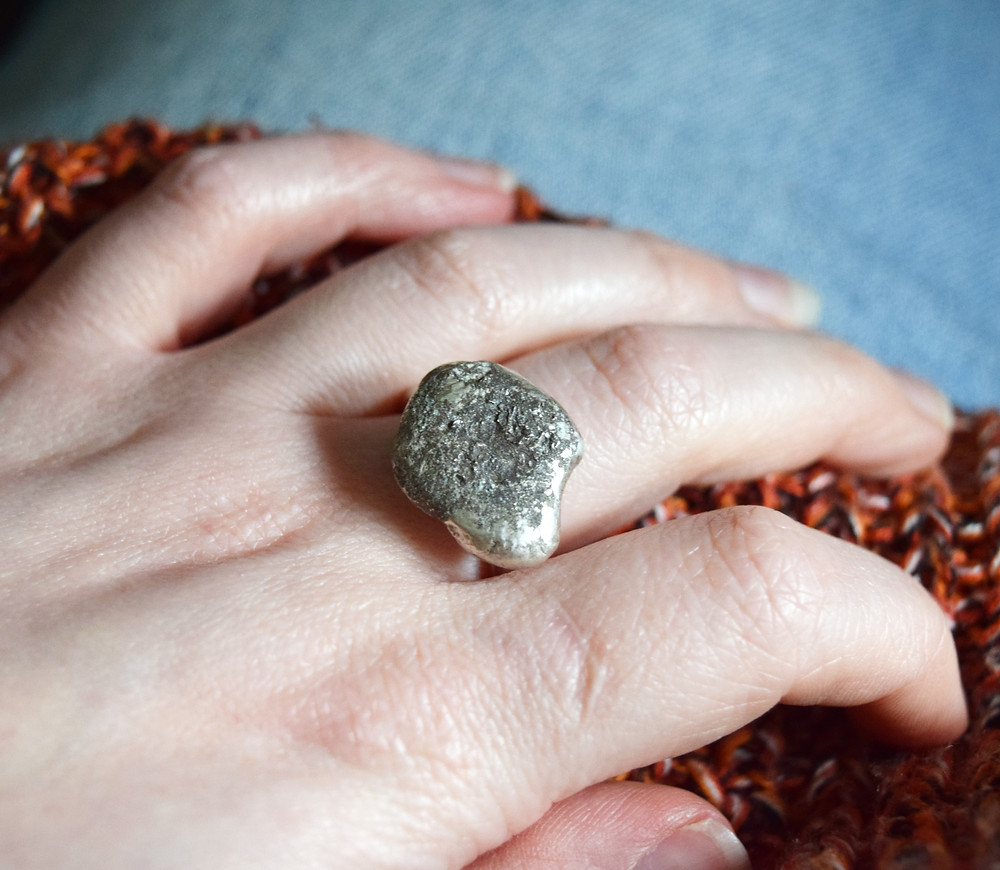 The image shows Emily wearing a chunky silver ring that features a large pebble created from recycled silver. Her hand is placed on her leg an you can see her pale blue jeans and her orange jumper.