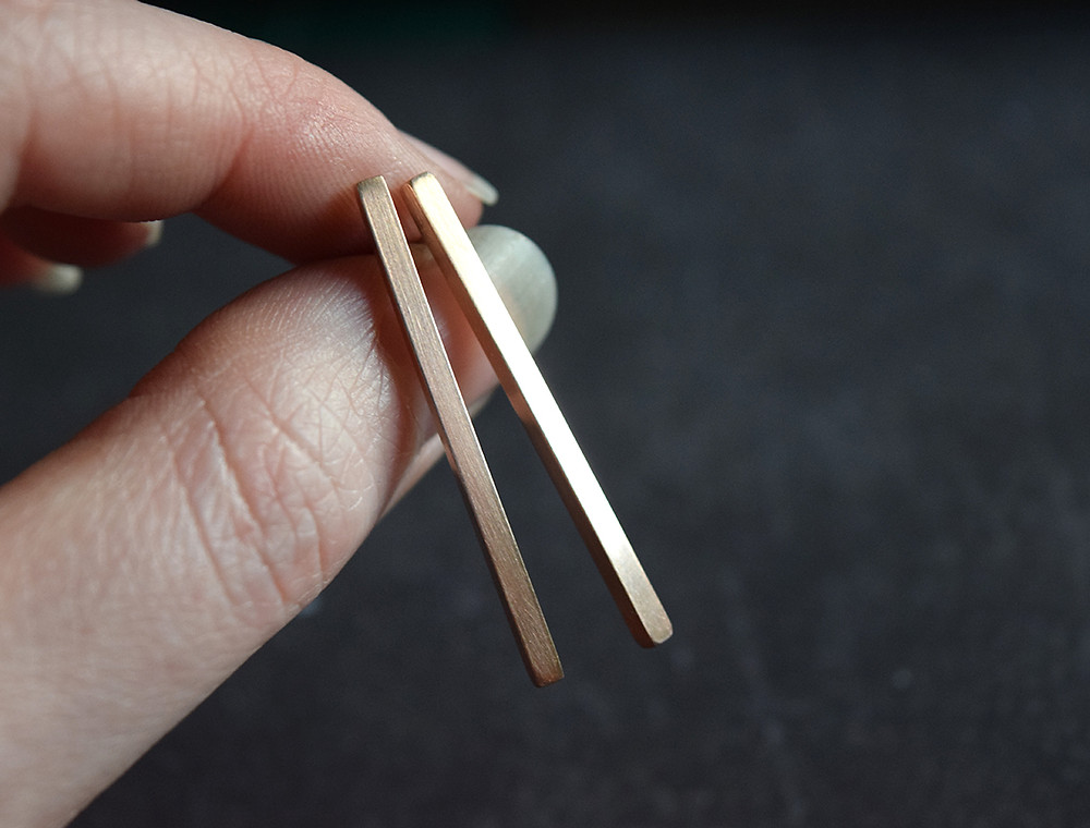 The photo is of a pair of thin rose gold bar stud earrings.The are being held between Emily's finger and thumb and are shown against a black background.