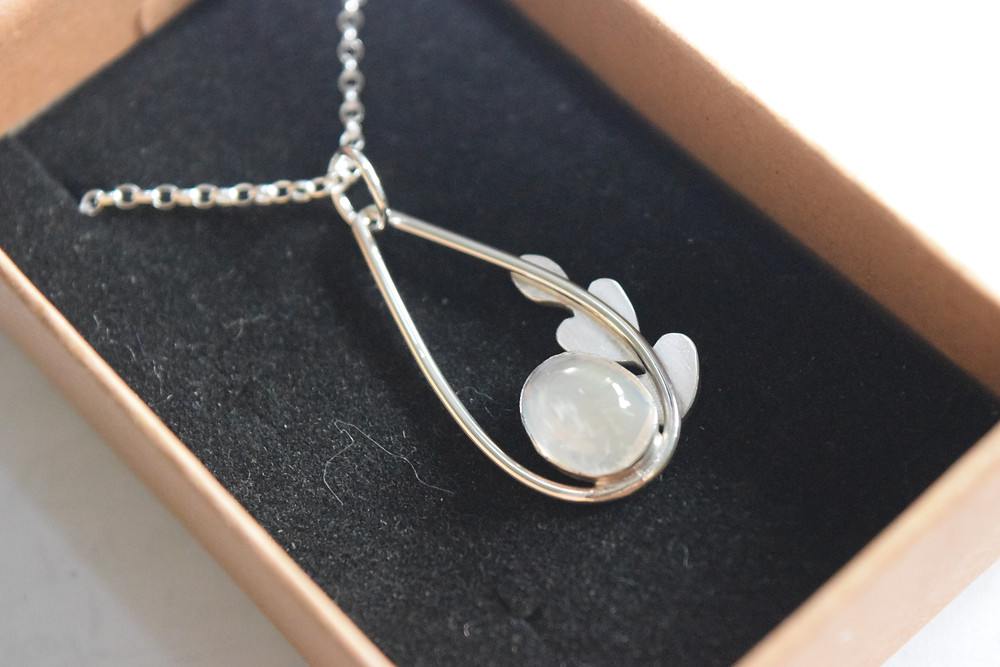A small silver pendant in a brown paper box with a black velvet cushion. The pendant is a small teardrop shape with an oval stone set in the bottom. The stone is clear but shines different colours in the light. There is a small set of three simple leaves going up the right side. The pendant hangas from a simple silver chain.