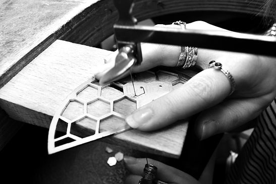 Emily sawing honeycomb shapes out of metal