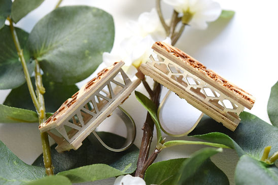 A pair of rings with a box made out of etched wood and cut our metal sides