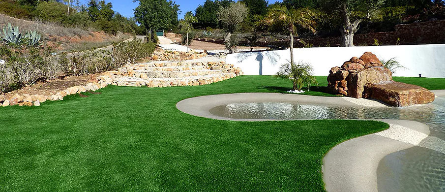 Algarve garden with free-form swimming pool, artificial grass, waterfall