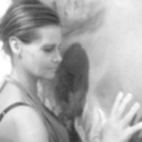 Photo noir et blanc du profil du visage et de sa main qui touche le tableau d'anany
