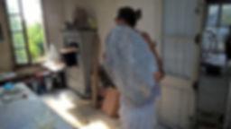Anany tient dansles main une création artistique ronde ressemble à une lune nacrée l'artiste anany est deboutdans son atelier artistique et son visage est en direction de la fenêtre ouverte sur la vue du mont ventoux