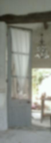 porte bleur et gris pastel et voilage en coton vue sur atelier et un lustre en cristal suspendu au plafond atelier d'anany artiste pein