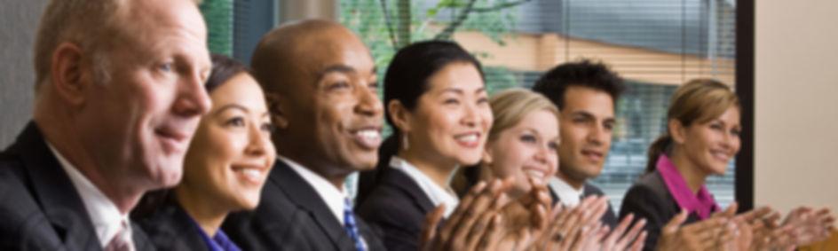 multi-ethnicco-workerssittinginarowappla