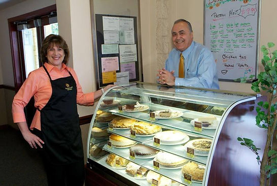 David and Debbie Shahvar standing next to a pie case featuring home made pies.