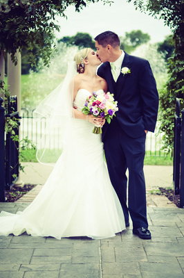 Outdoor ceremony kiss under arbor